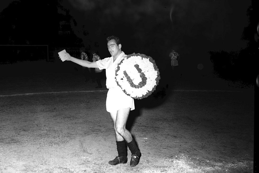 """Alberto """"Toto"""" Terry ingresando al campo de juego con un escudo de flores de su club Universitario de Deportes, previo a un partido contra Alianza Lima. Lima, 3 de enero de 1955. (Foto: GEC Archivo Histórico)"""