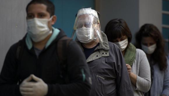 La gente usa mascarillas en la cola para usar un cajero automático en Buenos Aires, en medio de la pandemia del coronavirus COVID-19 (Foto de JUAN MABROMATA / AFP)