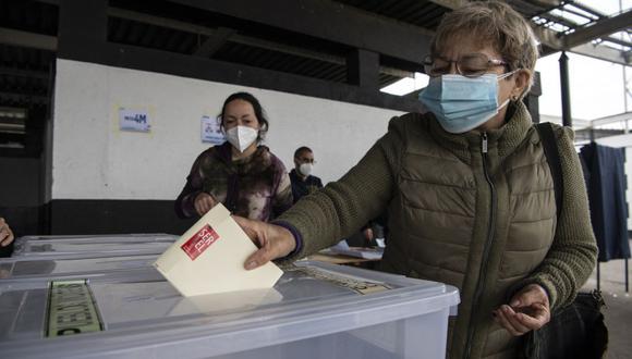 Una mujer emite su voto durante las elecciones para elegir alcaldes, concejales y una comisión para reescribir la Constitución de Chile. (Foto de Martín BERNETTI / AFP).