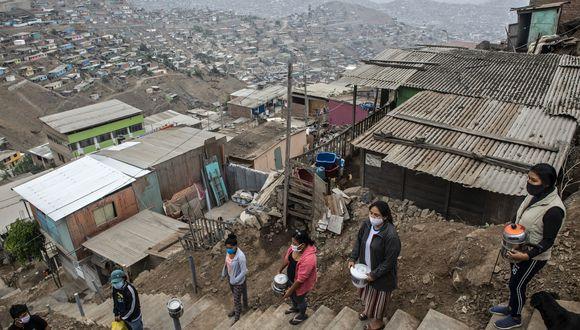 Las mujeres esperan para obtener comida en un comedor comunitario de Pamplona Alta, en Lima, Perú. (Foto por ERNESTO BENAVIDES / AFP).