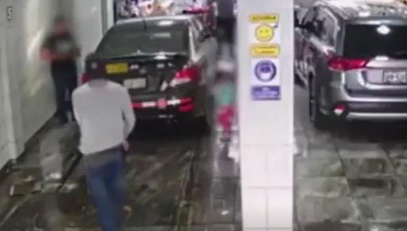 Momento en que uno de los delincuentes ingresa al local de lavado de autos y amenaza con un arma al taxista. (Captura: América Noticias)