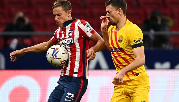 Barcelona's French defender Clement Lenglet (R) challenges Atletico Madrid's Spanish midfielder Marcos Llorente during the Spanish League football match between Club Atletico de Madrid and FC Barcelona at the Wanda Metropolitano stadium in Madrid on November 21, 2020. (Photo by GABRIEL BOUYS / AFP)
