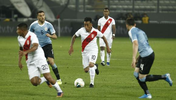 Christian Cueva conduce el balón ante la atenta mirada de los defensores uruguayos.