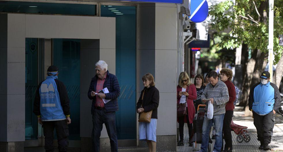 Algunas personas asisten a los bancos, con muchas precauciones por el coronavirus. | Foto: AFP