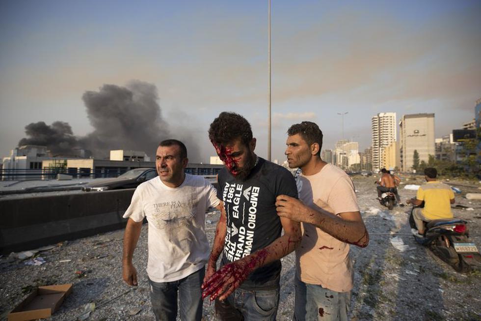 La gente ayuda a un hombre herido en una explosión masiva en Beirut. (Foto AP / Hassan Ammar).